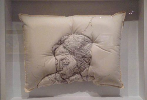 Törékeny alvó alakok párnába hímezve